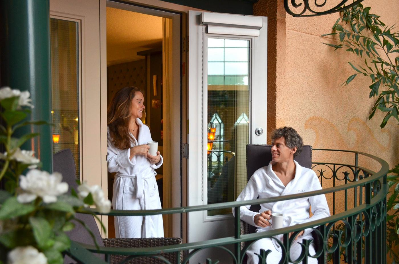 Couple in dressing gowns on the balcony of a room at the Hotel Palace Royal
